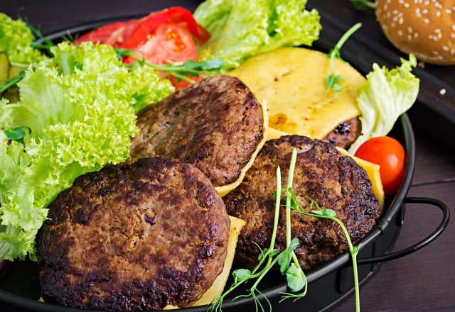 burger-cooking-burger-with-beef-tomato-cheese-pickled-cucumber-and-red-onion-on-plate.jpg